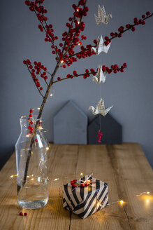 Wrapped present, twig of holly in vase and fairy lights - OJF00333