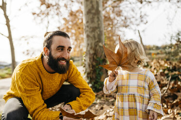 Father and daughter enjoying a morning day in the park in autumn, playing with autumn leaves - JRFF02255
