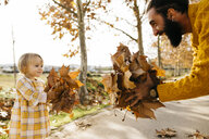 Father and daughter enjoying a morning day in the park in autumn, holding autumn leaves - JRFF02258