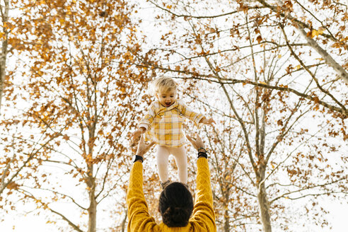 Father throwing his daughter in air, in a park in autumn - JRFF02264