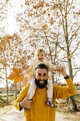 Father carrying his little daughter on shoulders in the morning in a park in autumn - JRFF02267