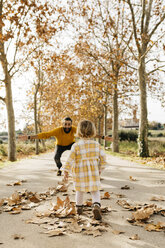 Father and daughter enjoying a morning day in the park in autumn - JRFF02270