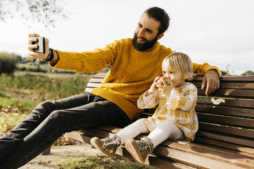 Father and daughter sitting on a bench in the park in autumn, father taking a selfie, daughter eating an apple - JRFF02273