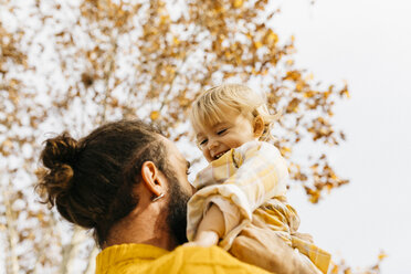 Father holding his daughter in the morning, in a park in autumn - JRFF02276