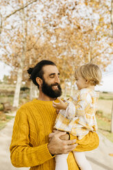 Father carrying his daughter on a morning day in the park in autumn - JRFF02279