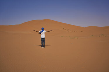 Morocco, back view of man standing on desert dune - EPF00514