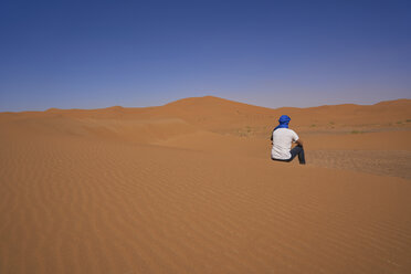 Morocco, back view of man sitting on  desert dune - EPF00517