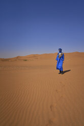 Morocco, man wearing blue kaftan and turban standing on desert dune - EPF00520