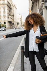 Young woman with laptop bag and coffee to go in the city, hailing a taxi - MAUF02134