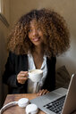 Young woman with laptop in a cafe, drinking a coffee - MAUF02146
