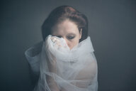 Studio shot of a woman wrapped in a white net - INGF11474