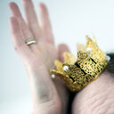 Close-up shot of a mini gold crown resting on a person's head - INGF11645