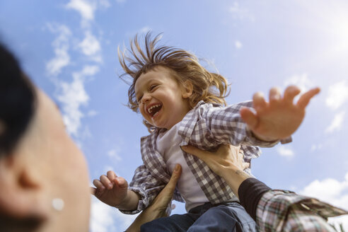 Mother lifting up happy toddler son outdoors - MGIF00294