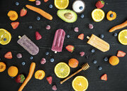 Three various sugar-free popsicles, fruits and vegetables on black wood - MBEF01456