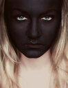 Portrait of a young woman with black face paint looking into the camera - INGF11679