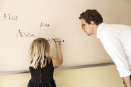 Male teacher watching girl practicing her name on whiteboard - ASTF00056