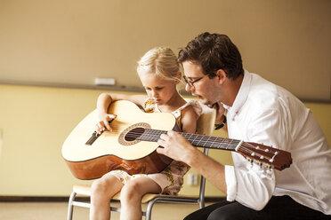 Male teacher teaching girl to play guitar - ASTF00059