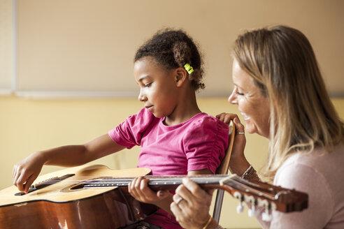Happy female teacher teaching girl to play guitar - ASTF00062