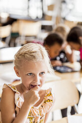 Thoughtful girl in classroom with classmates in background - ASTF00077