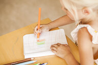 Cropped image of girl drawing with colored pencils in classroom - ASTF00083