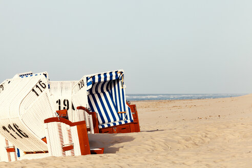 Tranquil scene of hooded chairs on a beach - INGF11742