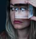 Close-up portrait of a young woman holding a clear cube to her face - INGF11751