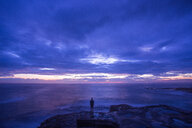 Silhouette of a man standing on a rock by the sea after a beautiful sunset - INGF11889