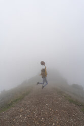 Woman hiking in the fog, jumping on a mountain path - AFVF02191