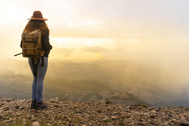 Woman with backback, standing on mountain, looking at view - AFVF02194