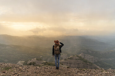 Woman with backback, standing on mountain, looking at view - AFVF02197