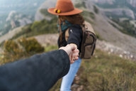 Woman with hat, standing on mountain, holding on to man's hand - AFVF02200