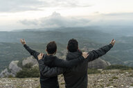 friends standing on mountain peak with arms around, enjoying he view - AFVF02203