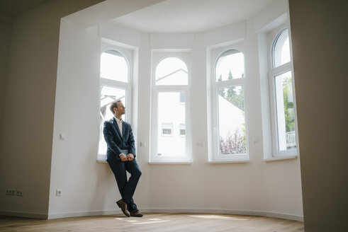 Estate agent waiting in newly refurbished home, holding laptop - KNSF05460
