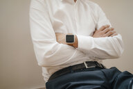 Mid section of a businessman wearing smartwatch with arms crossed - KNSF05472
