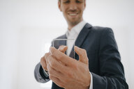 Businessman using glass touch screen in a new home - KNSF05478