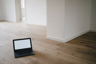 Laptop on wooden floor in a newly refurbished house - KNSF05481
