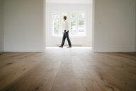 Businessman walking in empty flat - KNSF05499