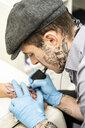 Tattoo artist tattoing hand - DAMF00027