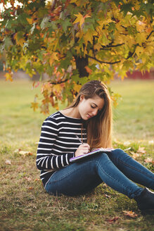 Young woman with notebook sitting on  meadow in a park in autumn taking notes - LOTF00007