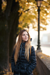 Young blonde woman standing in a street with trees behind during autumn. Italy, Veneto, Verona. - LOTF00010