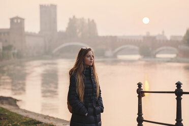 Young blonde woman standing next to river Adige during a sunset in Verona. Italy, Veneto, Verona. - LOTF00013