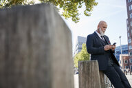 Elegant businessman leaning on wall in the city, using smartphone - RHF02383