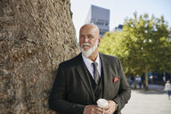 Elegant businessman leaning on tree in the city, drinking coffee - RHF02395