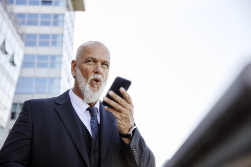 Elegant businessman in the city, using smartphone - RHF02404