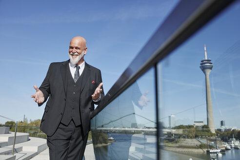 Elegant businessman standing on a bridge, making inviting gesture - RHF02428