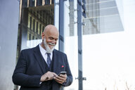 Elegant businessman using smartphone in the city - RHF02440