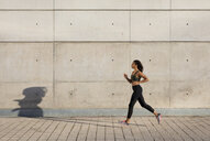 Young woman running along concrete wall in the city - MAUF02150