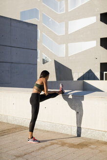 Young woman doing stretching exercise in the city - MAUF02159