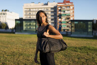 Sporty young woman with bag standing on meadow the city - MAUF02171