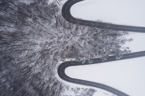 Austria, Wienerwald, winding road in snow-covered landscape, aerial view - HMEF00169